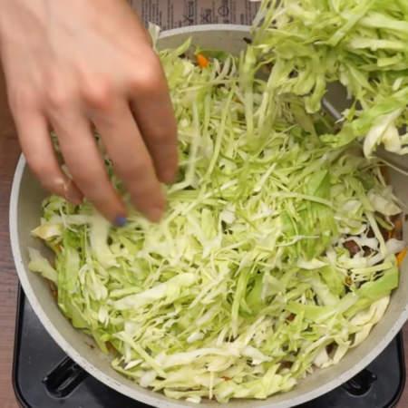 В сковороду кладем нашинкованную капусту. Все солим по вкусу и перемешиваем.