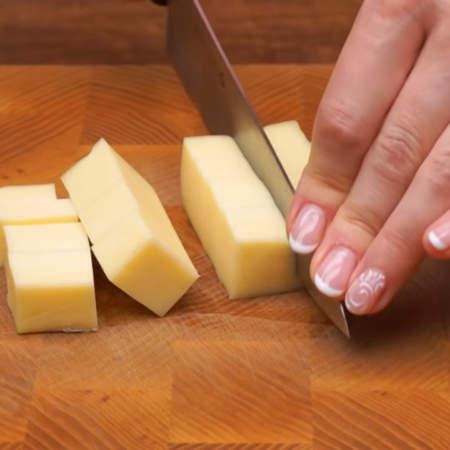 200 г сыра нарезаем кубиками размером примерно 1.5 см. Лучше всего для закуски брать сыр, а не сырный продукт.