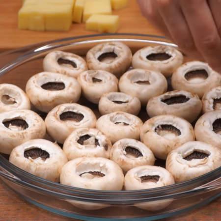 Подготовленные грибы выкладываем в форму для запекания или на противень шляпками вниз. Грибы немного солим.