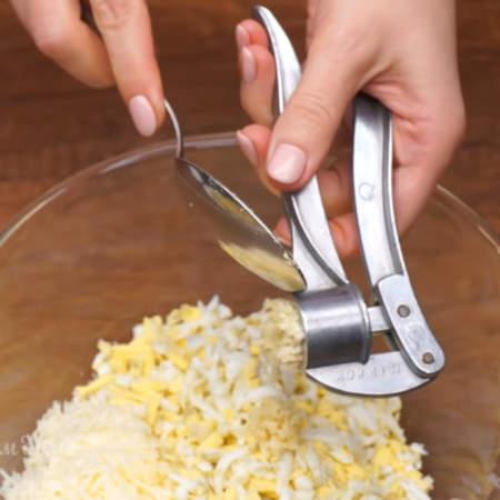 В миску кладем тертый сыр и яйца. Сюда же выдавливаем через пресс 2 зубчика чеснока.