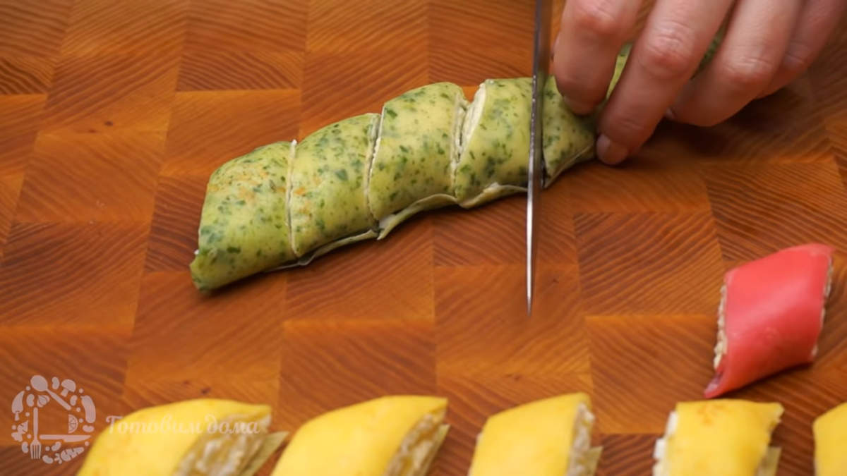 Готовые блины с начинкой нарезаем порционными кусками. Закуску красиво раскладываем на блюде и подаем на стол.