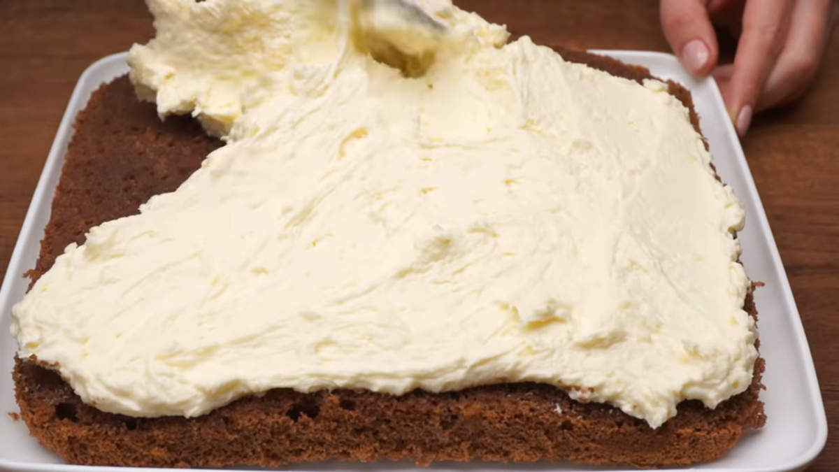 Сверху на бисквит выкладываем приготовленный заварной крем и аккуратно его разравниваем по всей поверхности.