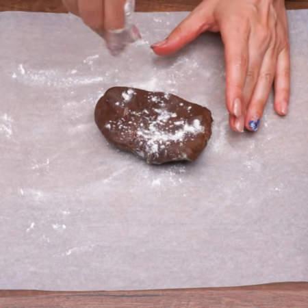 Тесто отлежалось в холодильнике, отрываем от него небольшой кусок и раскатываем на пергаментной бумаге, немного посыпанной мукой.