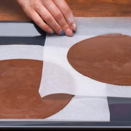 Готовое раскатанное тесто на пергаментной бумаге кладем на противень. Я выпекаю по два коржа за один раз.