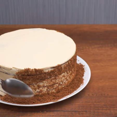 Крошкой посыпаем бока торта. Сначала накладываем крошку на бока торта с помощью ложки