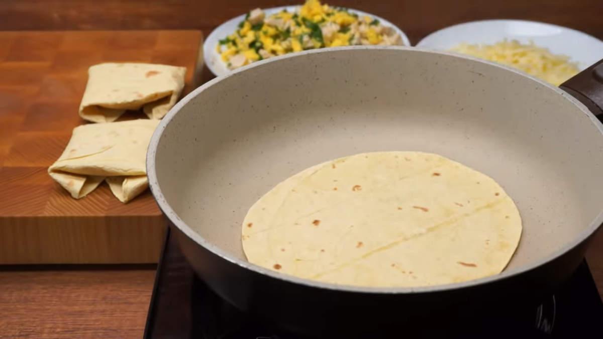 Берем тортилью - это тонкая лепешка для тако, и разогреваем ее на сковороде, чтобы она стала более пластичной и хорошо гнулась.