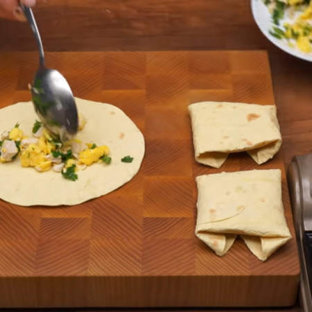 Теплую лепешку быстро кладем на доску и сразу же выкладываем на нее начинку с яйцами и мясом.