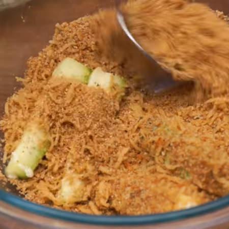 Затем эти брусочки перекладываем в панировку из сухарей с сыром и хорошо посыпаем их со всей сторон.