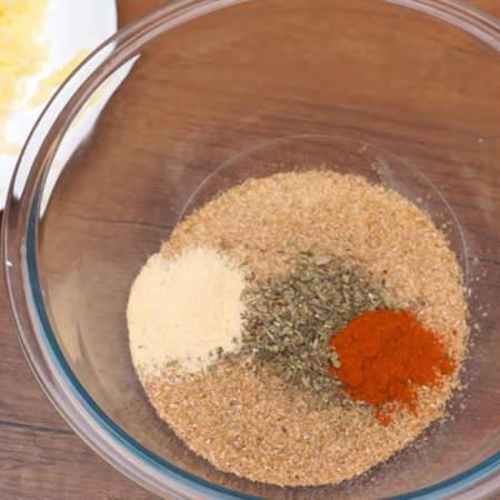 В сухую миску насыпаем 150 г панировочных сухарей, добавляем 1 ч.л. итальянских или прованских трав, 1 ч.л. молотой сладкой паприки и 1 ч.л. сухого чеснока. Также сюда добавляем тертый сыр.