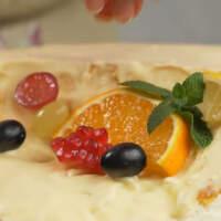 Фруктов выкладываем столько, чтобы они закрыли весь срез. Также украшаем торт листиками мяты.