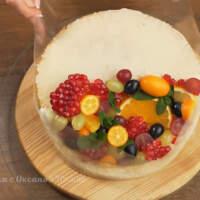 Торт плотно оборачиваем ацетатной пленкой. Сверху надеваем кулинарное кольцо. Сжимаем его до размера торта.