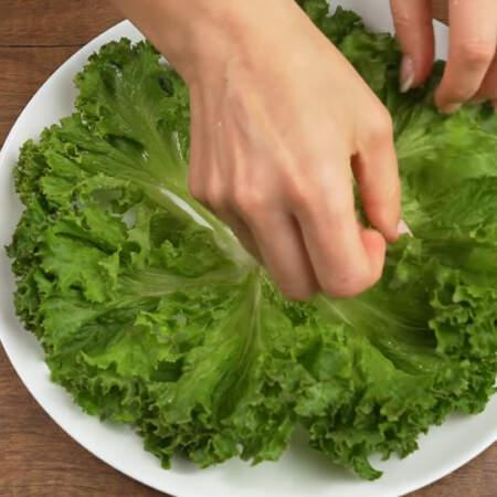 На большое плоское блюдо выкладываем по кругу листья салата.
