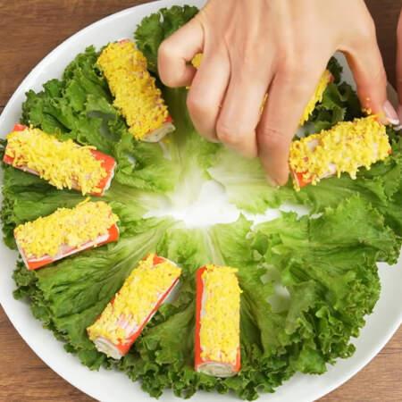 По кругу, на салатные листья, оставляя небольшое расстояние выкладываем начиненные крабовые палочки.