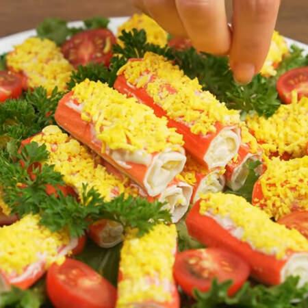 Серединку с крабовыми палочками украшаем листиками петрушки.  Если не хватает времени, то ее можно подавать без зелени, просто сложив на тарелочку.