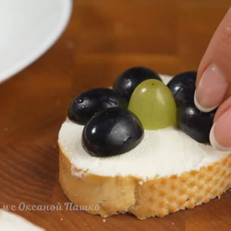 Сверху на бутерброд выкладываем виноград в виде красивого цветка. В центр кладем половинку винограда зеленого цвета. По кругу выкладываем половинки винограда темного цвета.