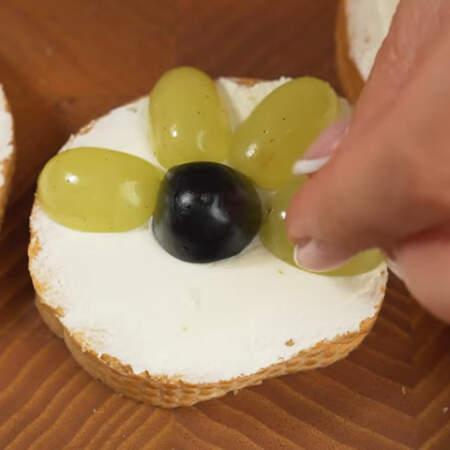 Вторую часть бутербродов украшаем наоборот. В центр кладем половинку темного винограда, а по кругу выкладываем зеленый виноград. Таким образом готовим все бутерброды.