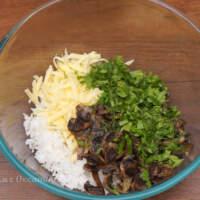 В миске смешиваем вареный рис, тертый сыр, жареные грибы с луком и нарезанную зелень.