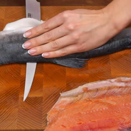 Второй кусок рыбы с хребтом переворачиваем на доску, хребтом вниз. И опять срезаем ножом филе вдоль хребта.