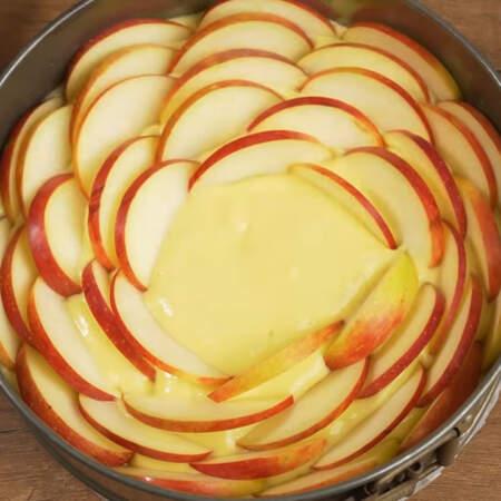 Сверху в тесто вставляем пластинки яблок.  Вставляем их по кругу до самого центра имитируя цветок.