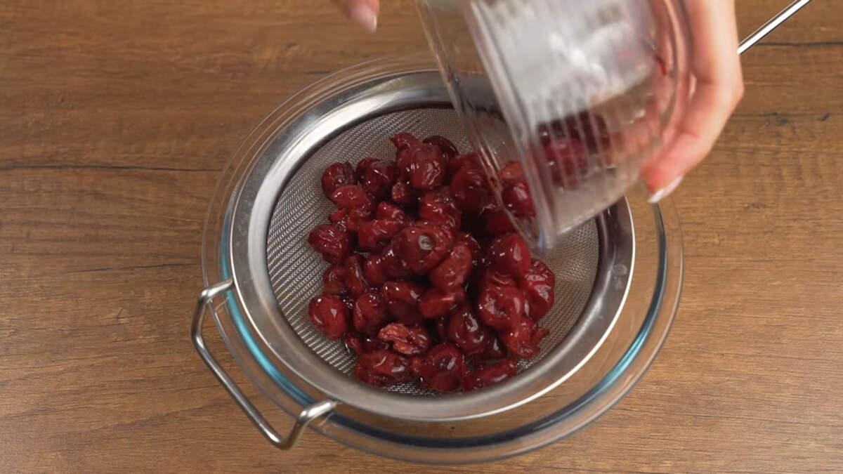 Пока печется бисквит приготовим вишневое желе для прослойки. На сито насыпаем 400 г замороженной вишни без косточек, чтобы стек сок.