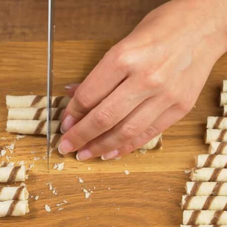 По бокам торт будем украшать вафельными трубочками.  Трубочки делаем такой длины, чтобы они выступали выше торта примерно на 1 см. Одну трубочку берем за шаблон и обрезаем все трубочки. Для украшения торта мне понадобилось 650 г таких трубочек.