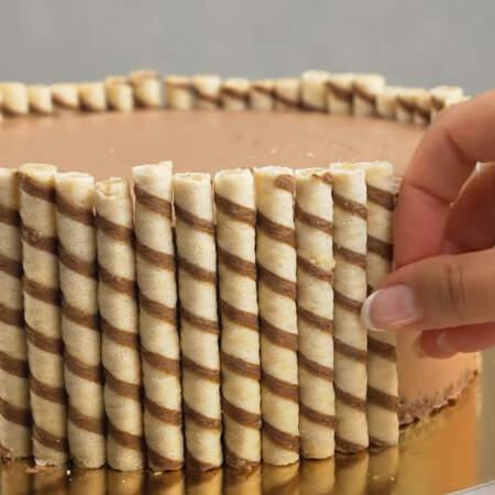 Подготовленные вафельные трубочки выставляем по кругу торта.  Они хорошо приклеиваются к крему, которым обмазали торт.