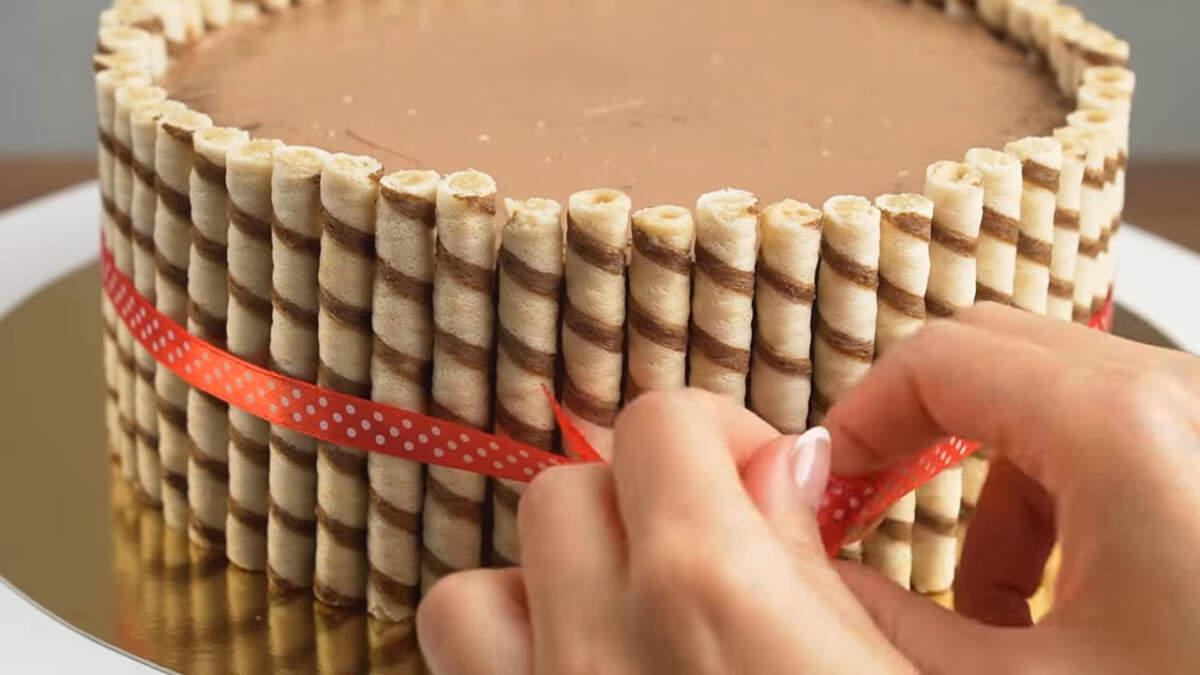 Торт перевязываем красивой ленточкой.  Это придаст ему еще более праздничный и красивый вид.  Также ленточка не даст отклеится трубочкам, если торт придется переносить.