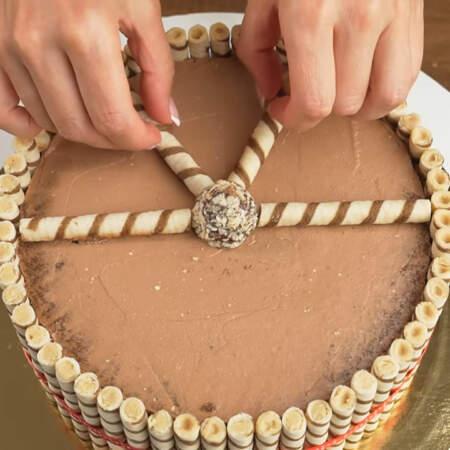 Сверху торт с помощью вафельных трубочек делим на 6 частей. По середине ставим конфету.
