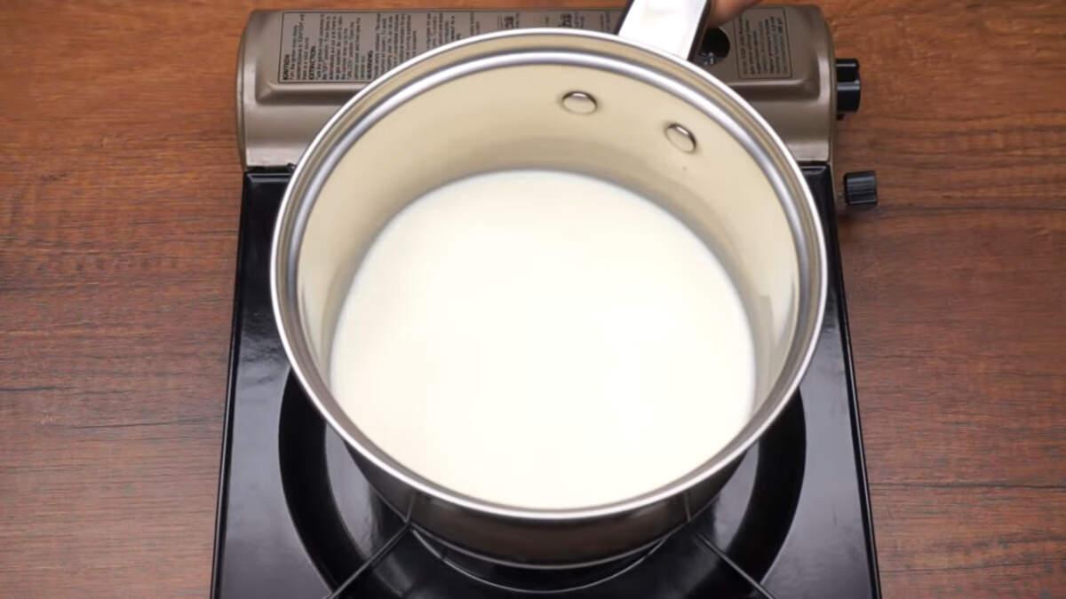 Сначала приготовим заварной крем для десерта. В сотейник наливаем примерно 250 мл молока и ставим на огонь закипать.