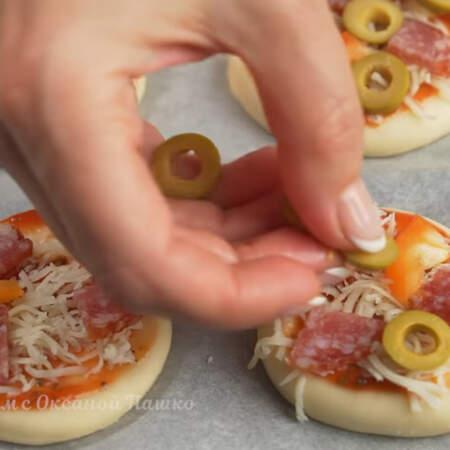 Кладем 2-3 кусочка колбасы, также кладем перец и по нескольку колечек нарезанных оливок.