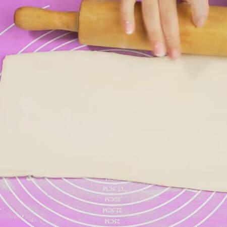 Берем лист готового бездрожжевого слоеного теста. Раскатываем его в ширину до тех пор, пока оно не увеличится по ширине примерно в 2 раза.