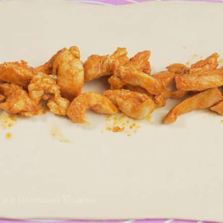 На раскатанное тесто примерно посередине вдоль кладем половину обжаренного куриного мяса.