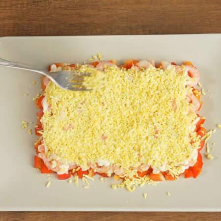 Следующим слоем кладем тертый желток. Примерно третью часть желтка оставляем для украшения салата.