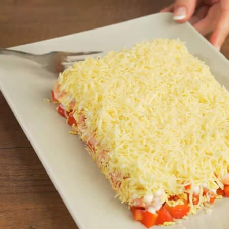 Следующим слоем кладем тертый сыр. Весь салат выравниваем вилкой.