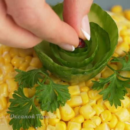 Сверху на салат ставим цветок из огурца. Вокруг цветка кладем листики петрушки.  В центр цветка для красоты кладем зернышко граната.