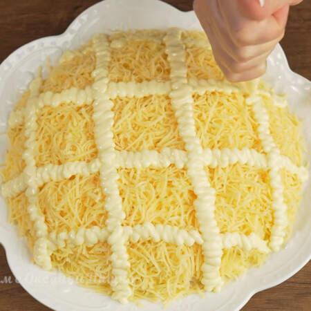 На сырный слой наносим широкие полосы из майонеза сначала вдоль, а затем поперек,  в виде квадратов.