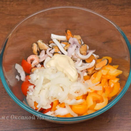 В миску кладем подготовленные помидоры, нарезанный перец и 400 г морского коктейля, предварительно слив с него жидкость. Сюда же добавляем маринованный лук.  Салат немного солим и заправляем 2 ст.л. майонеза.