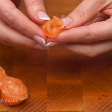 Салат перекладываем на тарелку, на которой будем подавать его на стол. Из полосок рыбы скручиваем розочки.
