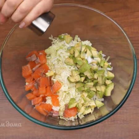 В миску кладем нашинкованную капусту, нарезанную рыбу и подготовленное авокадо. Салат солим по вкусу и перчим, не забывайте, что рыба и майонез уже соленые.