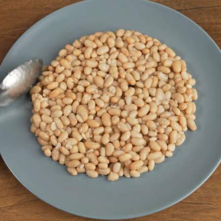 На дно плоского блюда кладем вареную белую фасоль. Я использую консервированную фасоль из банки. Диаметр моего блюда 26 см. Фасоль аккуратно распределяем по блюду формируя из нее круг.