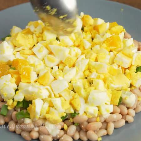 Следующим слоем кладем нарезанные яйца.  Стараемся выкладывать так, чтобы каждый последующий слой лежал поверх предыдущего не закрывая его по бокам.  Если рыба не сильно соленая, то яйца можно немного посолить.