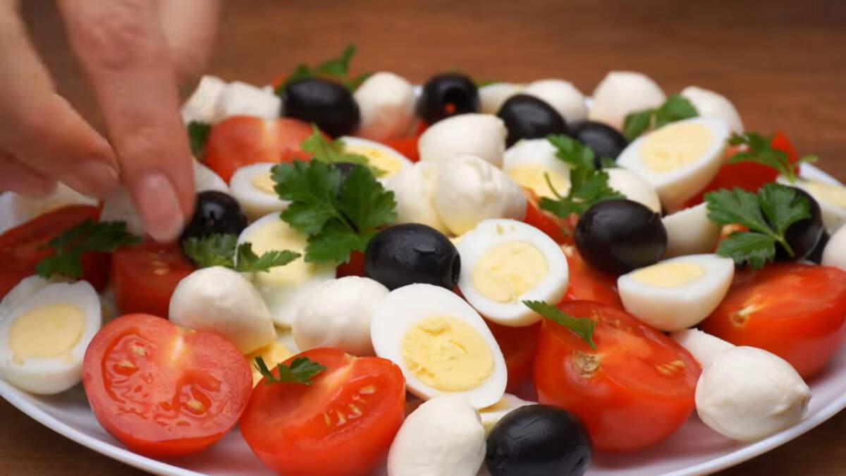 Выкладываем оставшиеся черные маслины. Черных маслин понадобится одна трехсот граммовая баночка. Также на салат выкладываем листики свежей петрушки.