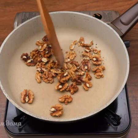 Пока маринуется лук подготовим остальные ингредиенты для салата. 50 г грецких орехов высыпаем на сковороду и немного обжариваем их на небольшом огне периодически перемешивая.