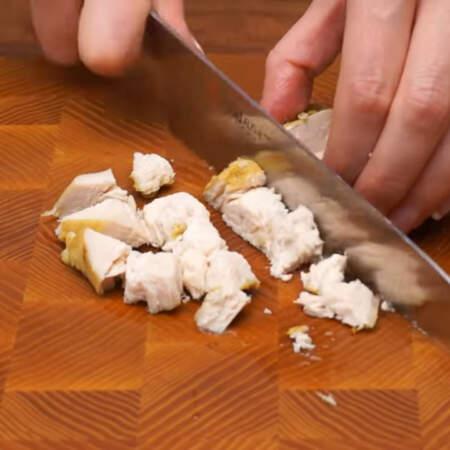 Остывшее куриное филе нарезаем сначала вдоль на пластинки, а затем нарезаем небольшими кубиками.
