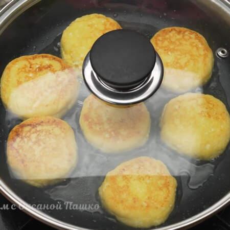 Убавляем огонь до минимального и накрываем сковороду крышкой. Так готовим сырники примерно 2-3 минуты.