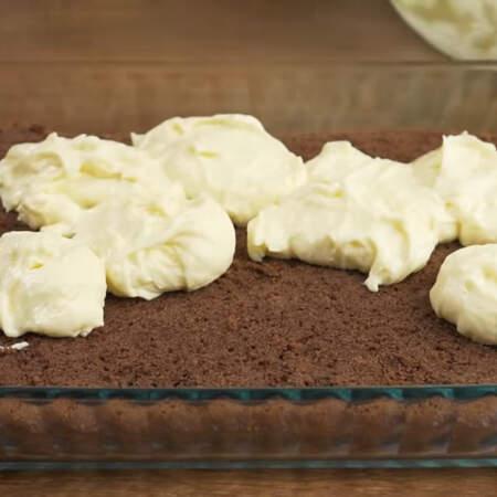 Низ бисквита кладем обратно в форму, в которой он выпекался. Половину крема из миски выкладываем на бисквит