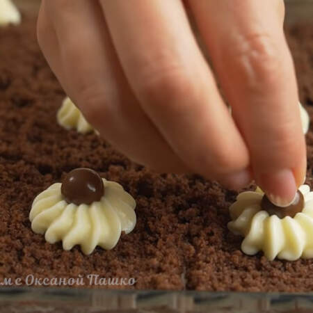 На крем кладем круглую шоколадную конфетку. Торт опять ставим в холодильник застывать и пропитываться на 2 часа.
