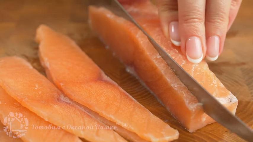 Сначала подготовим рыбу.  Для рулета понадобится примерно 250 г соленой красной рыбы. Нарезаем ее на тонкие пластинки.  Для того, чтобы рыбу было удобнее резать, её можно немного подморозить, положив в морозильную камеру примерно на полчаса или час.