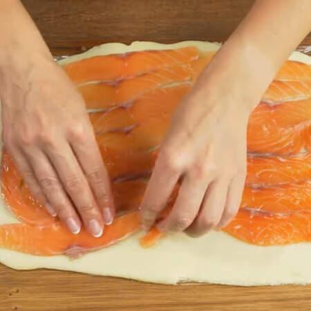 Снимаем верхнюю пищевую пленку с сыра.  На сырный пласт выкладываем плотно друг к другу нарезанные кусочки рыбы.  По одной из длинный сторон не докладываем рыбу до края на пару сантиметров, чтобы рулет лучше закрутился.