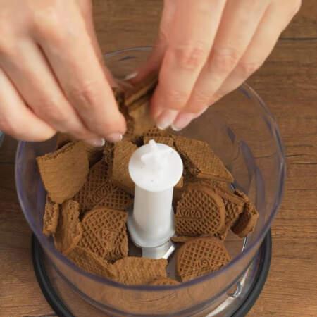 Сначала приготовим основу для торта. 250 г шоколадного песочного печенья немного ломаем и кладем в чашу измельчителя.